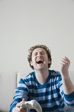 Uomo che ride mentre tenendo la console del video gioco Fotografia Stock