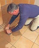 Uomo che riempie di malta un pavimento non tappezzato di ceramica Immagini Stock Libere da Diritti