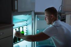 Uomo che rimuove bottiglia di birra dal frigorifero Immagine Stock Libera da Diritti