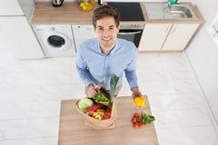 Uomo che rimuove le verdure dalla borsa di drogheria Fotografie Stock