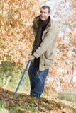 Uomo che riordina i fogli di autunno Immagini Stock