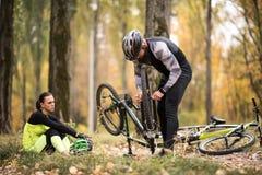 Uomo che ripara bici in parco fotografia stock