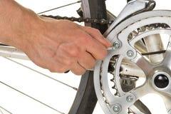 Uomo che ripara chainring su una bicicletta Fotografia Stock Libera da Diritti