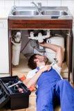 Uomo che ripara il lavandino di cucina Fotografia Stock