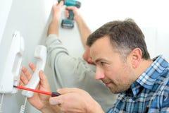 Uomo che ripara il telefono del citofono fotografie stock