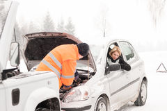 Uomo che ripara inverno di assistenza della neve dell'automobile della donna Immagine Stock Libera da Diritti
