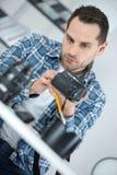 Uomo che ripara una macchina fotografica immagine stock