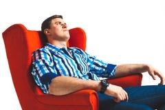 uomo che riposa nella sedia del bracciolo Fotografia Stock