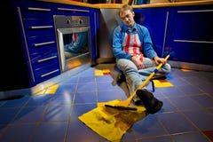 Uomo che riposa sul pavimento della cucina Fotografia Stock
