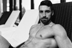 Uomo che riposa sulle chaise-lounge di Sun dalla piscina Immagine Stock Libera da Diritti