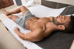 Uomo che riposa sulle chaise-lounge di Sun dalla piscina Fotografia Stock Libera da Diritti