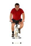 Uomo che risolve con una bici statica Fotografia Stock