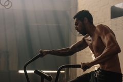 Uomo che risolve sulla bici di esercizio alla palestra Fotografia Stock