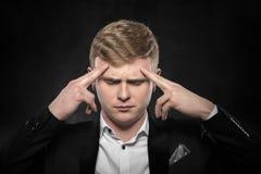 Uomo che ritiene un'emicrania o intensamente che pensa Immagini Stock