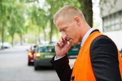 Uomo che rivolge al cellulare dopo l'incidente stradale Fotografia Stock