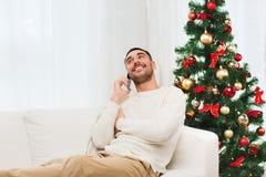 Uomo che rivolge allo smartphone a casa per natale Fotografia Stock