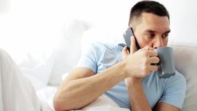 Uomo che rivolge allo smartphone a letto a casa archivi video