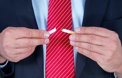 Uomo che rompe sigaretta in due Fotografia Stock