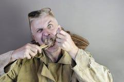 Uomo che rosicchia un osso Fotografia Stock Libera da Diritti