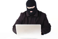 Uomo che ruba i dati da un computer portatile immagini stock