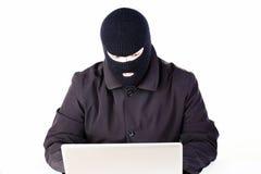 Uomo che ruba i dati da un computer portatile fotografie stock