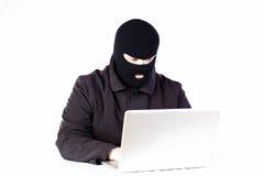 Uomo che ruba i dati da un computer portatile immagini stock libere da diritti