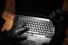 Uomo che ruba i dati da un computer portatile fotografia stock
