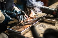 Uomo che salda due pezzi di metallo con fuoco immagini stock libere da diritti
