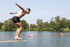 Uomo che salta giù trampolino alla piscina Immagini Stock