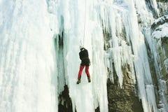 Uomo che scala cascata congelata fotografia stock