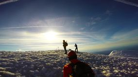 Uomo che scala la piccozza da ghiaccio ed i ramponi della montagna di Snowy video d archivio