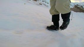Uomo che scala la piccozza da ghiaccio ed i ramponi della montagna di Snowy stock footage