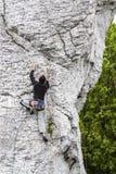 Uomo che scala parete rocciosa ripida Fotografie Stock Libere da Diritti