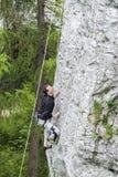 Uomo che scala parete rocciosa ripida ed alta Fotografie Stock Libere da Diritti