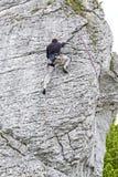 Uomo che scala parete rocciosa ripida ed alta Fotografia Stock