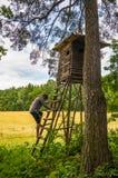 Uomo che scala sulla capanna del cacciatore Fotografia Stock
