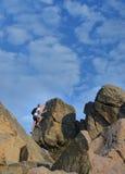 Uomo che scala un'alta parete rocciosa Immagini Stock