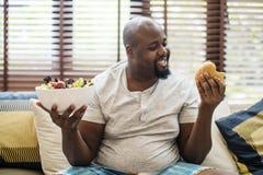 Uomo che sceglie che cosa mangiare Immagini Stock