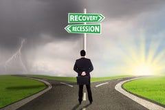Uomo che sceglie la strada alla finanza di recessione o di recupero Fotografia Stock Libera da Diritti