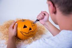 Uomo che scolpisce la Jack-O-lanterna della zucca per il partito di Halloween Immagine Stock Libera da Diritti