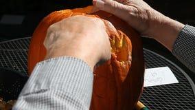 Uomo che scolpisce la zucca di Halloween archivi video