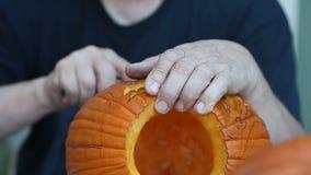 Uomo che scolpisce progettazione complessa sulla zucca di Halloween archivi video
