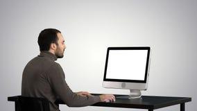 Uomo che scrive sul computer sul fondo di pendenza fotografia stock libera da diritti