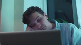 Uomo che scrive sul computer portatile che si siede vicino alla finestra stock footage