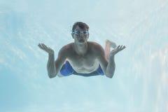 Uomo che scrolla le spalle le spalle underwater nella piscina Fotografie Stock