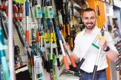 Uomo che seleziona gli strumenti della famiglia in deposito Fotografie Stock