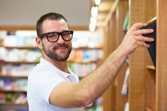 Uomo che seleziona un libro in una biblioteca Fotografia Stock