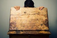 Uomo che sembra lo scrittorio interno della vecchia scuola Fotografie Stock Libere da Diritti