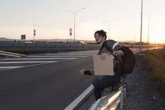 Uomo che sfoglia su un cartone vuoto della strada fotografia stock
