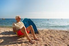 Uomo che si accampa alla spiaggia Immagini Stock